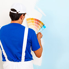 Man comparing paint samples to wall color