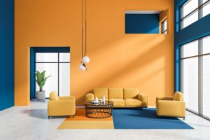 a decorated living room with contrasting colored furniture and walls