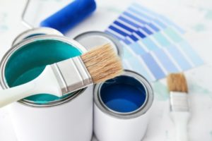 different paint swatches of blue laying on a counter with two paintbrushes and two cans of blue paint