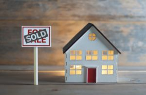 """a small model home with a """"for sale"""" sign in front of it and a """"sold"""" sticker placed over the sign"""