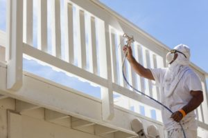 person painting the deck of a patio outside