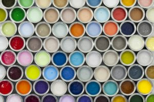 all different colors of paint samples sitting next to each other in canisters